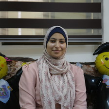 A woman poses with two balloon graduates