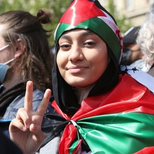 A woman draped in the Palestinian flags gives the victory sign