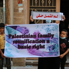 """Two children hold a poster reading """"Palestinian family reunification is a basic right"""""""