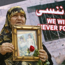 Woman holds framed photo of young man and rose in front of banner reading We will never forget in English and Arabic