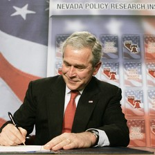 George W. Bush smirks as he signs document while sitting at table with American flag backdrop behind him