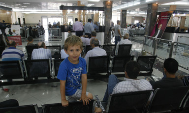 Palestinians wait at the Rafah border crossing to travel from Gaza to Egypt