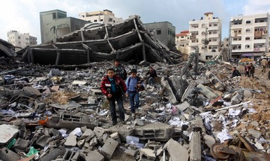 Two boys standing in the middle of rubble