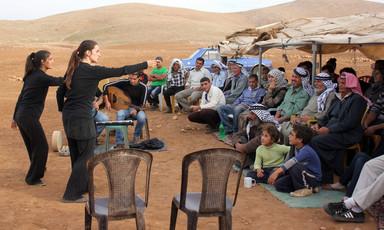 Women in black gesture towards audience in outdoor setting