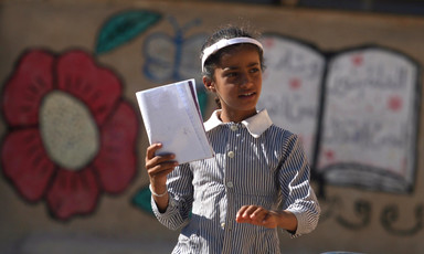Girl in school uniform holds book