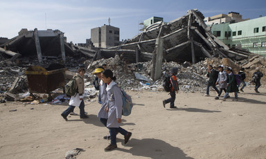 Children walk past rubble of destroyed buildings