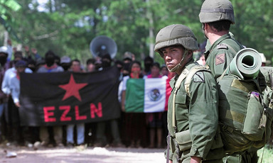 Mexican soldiers stand in front of crowd of protesters holding flags