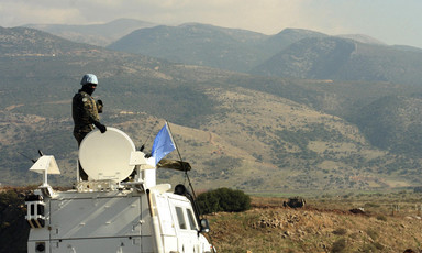 UN soldier atop armored vehicle overlooks Lebanon-Israel border