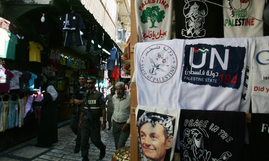 Israeli police walk by display of T-shirts marketed to tourists
