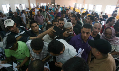 Men holding passports crowd at crossing terminal