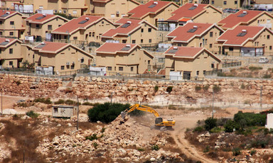 An earth-moving machine works in the foreground with Israeli settlement homes in background