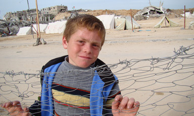 Boy leans against fence with destroyed homes in background