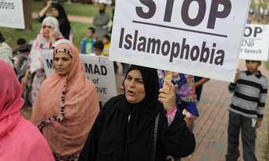 Woman carries sign reading Stop Islamophobia