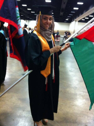 Young woman wearing graduation gown smiles while holding Palestinian flag