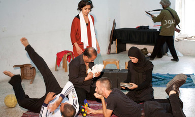 Scene from play shows family sitting together in foreground with Israeli soldier character in background