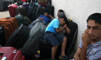 Men and boys sleep on suitcases