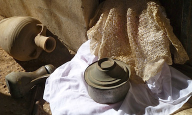 Vessels and pots sit on fabric
