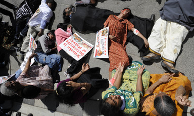 Women wearing mock blood lie on ground surrounded by other seated women