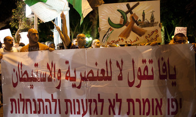 Men carry banner reading Yaffa says no to racism and settlements in Arabic and Hebrew