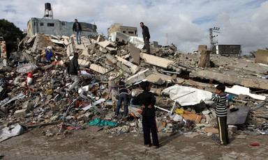 Children gather on rubble of building hit in Israeli air strike