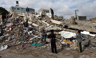Children gather on rubble of building hit in Israeli air strike