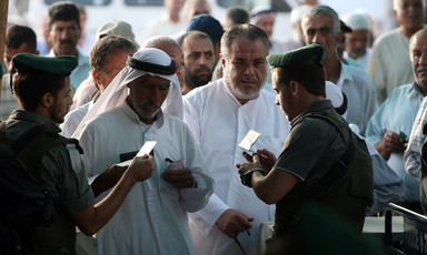 Israeli soldiers inspect the IDs of Palestinian men at a checkpoint