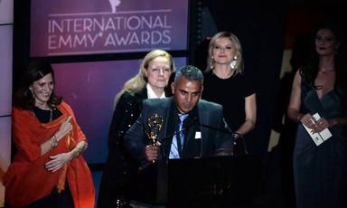 Man makes speech at podium while holding award