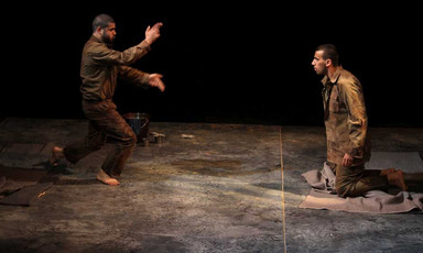 A standing man gestures to a kneeling man on a dark, spare stage