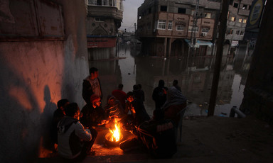 Men sit by campfire in flooded urban area