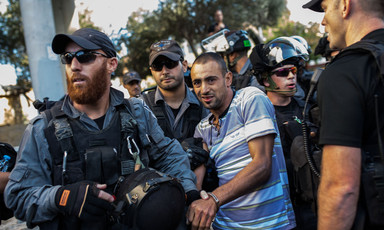 Israeli forces in riot gear arrest young man with blood smeared on his mouth