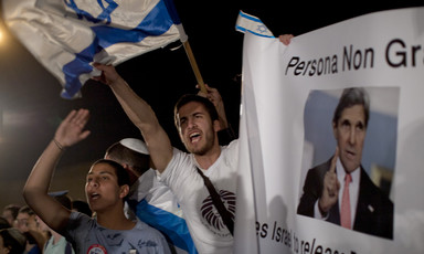 Young people wave Israeli flags during nighttime rally