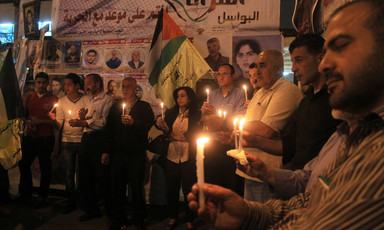 Crowd hold candles in tent covered with posters of political prisoners