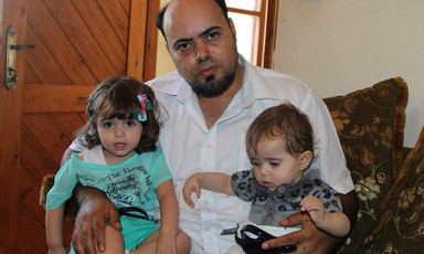 Photo shows Amjad Safadi sitting on couch holding two small girls