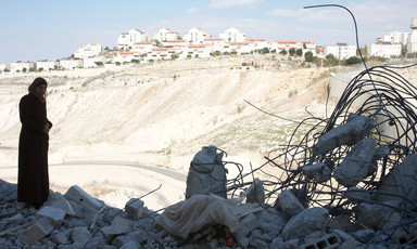Palestinian woman stands among rubble of destroyed home with Israeli settlement in background