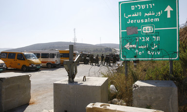 Photo shows highway sign for Route 443 with group of Israeli soldiers forming roadblock in background