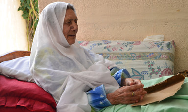 Elderly woman sits in bed