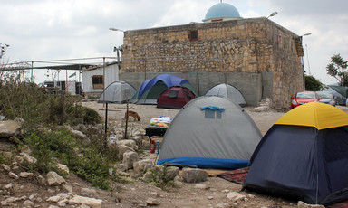 Photograph shows camping tents in front of old church built of stone