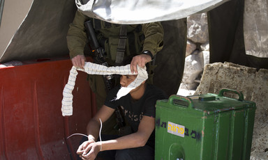Israeli soldier puts blind fold on zip-cuffed Palestinian youth