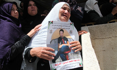 Mourning woman holds poster of slain child