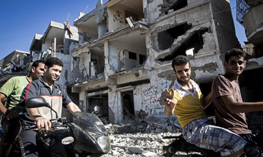 Smiling young men on motorbikes give victory sign in front of shelled building in Gaza City