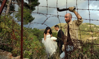Man with machete makes hole in barbed wire fence as couple dressed as bride and groom stand in background in natural landscape