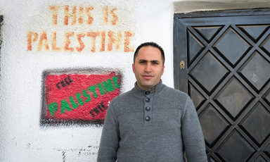 Young man stands in front of wall reading This is Palestine