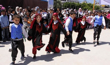 Boys and girls hold hands while performing a line dance