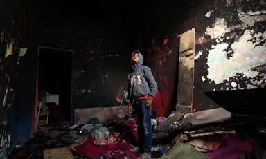 A boy stands in the middle of a room with charred walls and debris