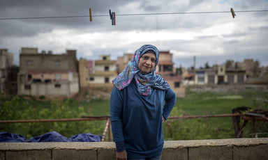 Smiling woman stands underneath clothes line outdoors with buildings and cloudy sky in background