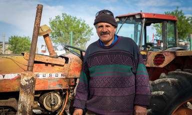 Smiling middle-aged man stands in front of farming equipment
