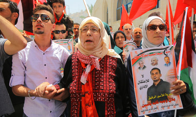 Elderly woman wearing traditional embroidered dress is flanked by two younger relatives at rally