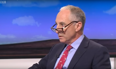 A man in a suit with glasses perched on the end of his nose talks to a TV presenter, who is offscreen.