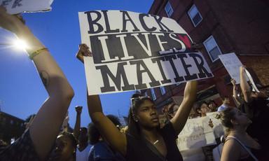 Woman holds sign reading Black Lives Matter during demonstration