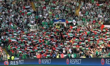 Dozens of football spectators hold up Palestinian flags in full stadium